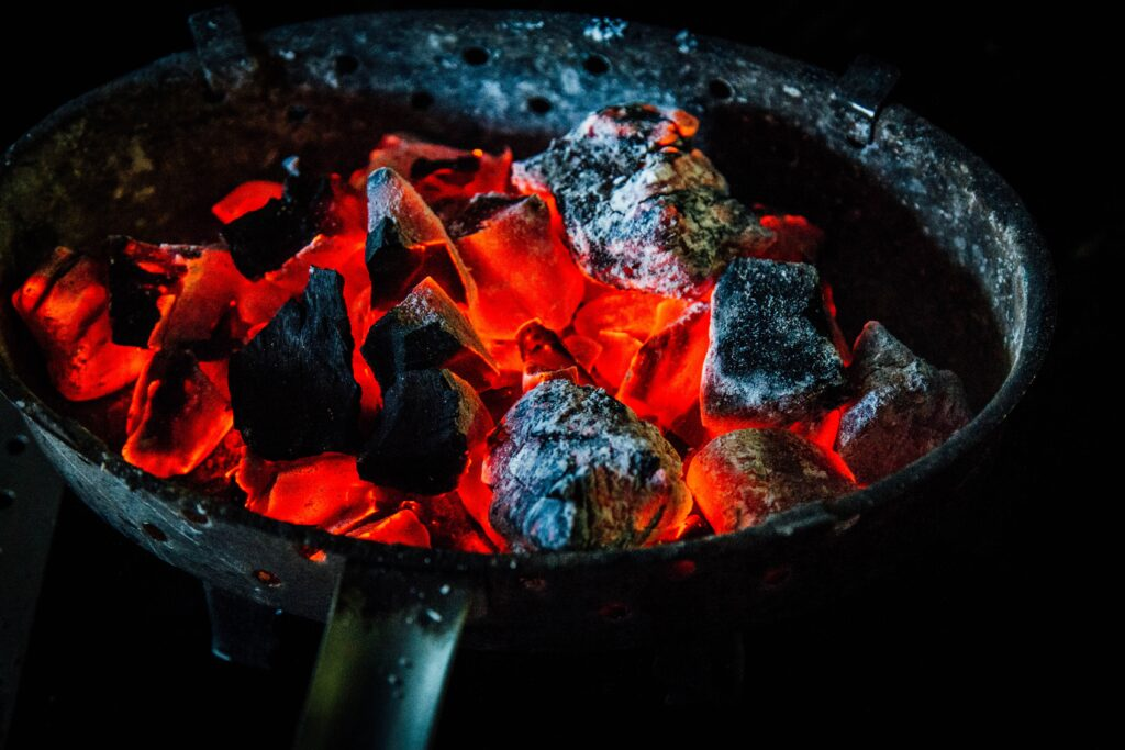 preheating a skillet to cook wagyu beef with charcoal pieces inside it