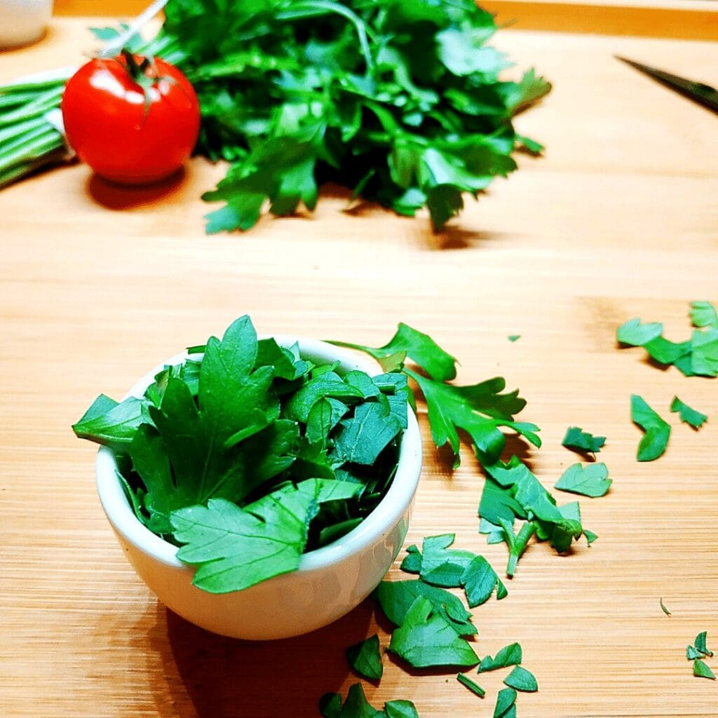 Always buy fresh parsley and use it as garnish or to add flavor to your meat soup. Pictured here is chopped parsley in a white bowl.